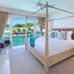 Home 504 Spacious Master bedroom with pool and island views at Port Ferdinand which are luxury marina residences for sale in Barbados